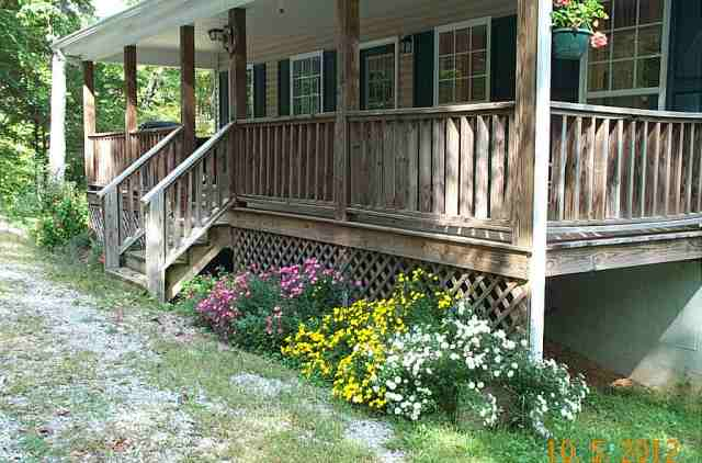 The other flower boxes are in front of the house and separate the house from the driveway.